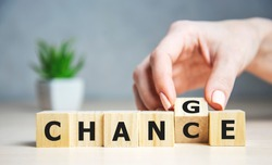 Businesswoman hand holding wooden cube with flip over block CHANGE to CHANCE word on table background. success, strategy, solution, business and Positive thinking concepts