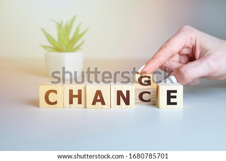 Businesswoman hand holding wooden cube with flip over block CHANGE to CHANCE word on table background. success, strategy, solution, business and Positive thinking concepts Stock photo ©