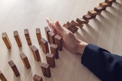 Businesswoman hand stopping the domino wooden effect concept for business.