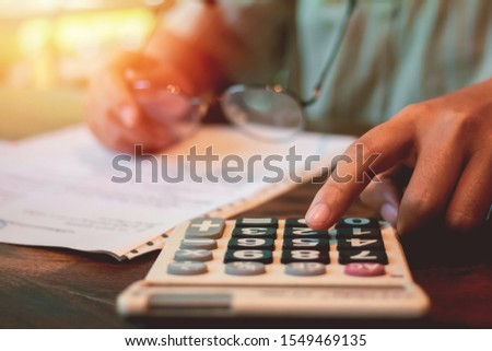 businesswoman hand using calculator Calculating bonus(Or other compensation) to employees to increase productivity. hand holding vintage glasses and sunset light background