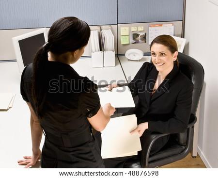 Businesswoman handing co-worker file folder