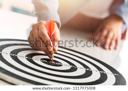 Businesswoman hands holding a darts aiming the target  business goal concept. #1317975008