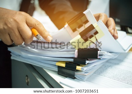 Businesswoman hands working on Stacks of documents files for finance in office. Business report papers or Piles of unfinished document achieves with black clip paper.Concept of Business Annual Reports #1007203651