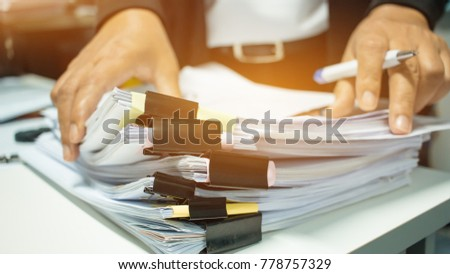 Businesswoman hands working on Stacks of documents files for finance in office. Business report papers or Piles of unfinished document achieves with black clip paper. Concept of Business Annual Report #778757329