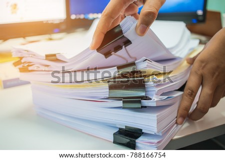 Businesswoman hands working on Stacks of documents files for finance in office. Business report papers or Piles of unfinished document achieves with black clip paper.concept of Business Annual Reports #788166754