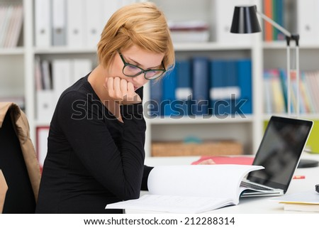 Businesswoman hard at work in the office sitting at her desk reading through paperwork with her chin resting on her hand
