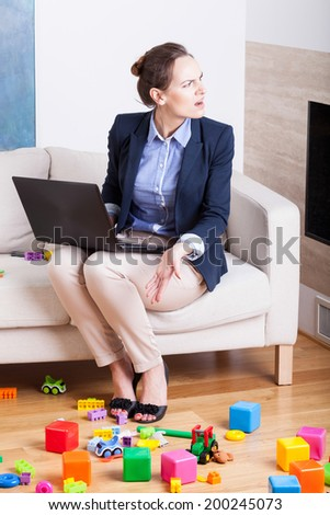 Businesswoman having a problem with concentrating on work at room full of kids toys