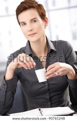 Businesswoman having coffee, with cup handheld, smiling at camera.?