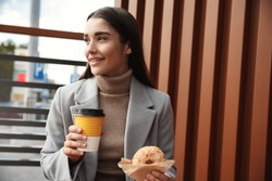 Businesswoman having lunch in outdoor cafe. Young woman eating donut and drinking coffee on street, stop in restaurant for a break.