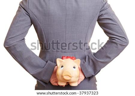 Businesswoman hiding a piggy bank behind her back