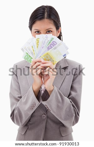Businesswoman hiding face behind money against a white background