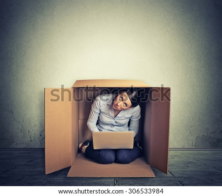 Businesswoman hiding in the box working on computer
