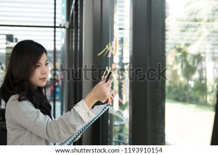 Businesswoman hold adhesive notes on glass wall in meeting room at workplace. Sticky note paper reminder schedule for discussing idea at office. business, brainstorming, creativity concept #1193910154