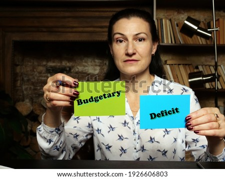 BusinessWoman holding a blank business cards. Business concept about Budgetary Deficit with phrase on the sheet. Stock photo ©