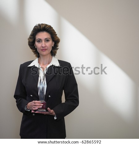 Businesswoman holding a glass trophy