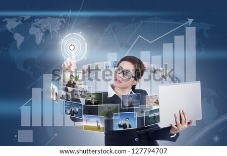 Businesswoman holding a laptop and pressing a touchscreen on profit bar chart background