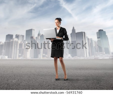 Businesswoman holding a laptop with cityscape on the background