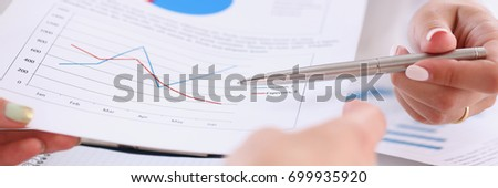 Businesswoman holding a silvery pen in her hand indicates the interlocutor for a digram on the form of annual report on the financing of organizations trains the processing of this statistical study #699935920