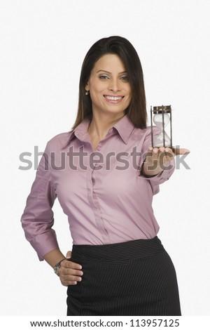 Businesswoman holding an hourglass