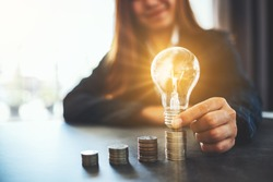 Businesswoman holding and putting lightbulb on coins stack on table for saving energy and money concept