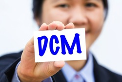 Businesswoman holding card with DCM message.