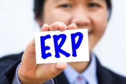 Businesswoman holding card with ERP message.