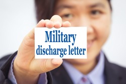 Businesswoman holding card with Military discharge letter message.