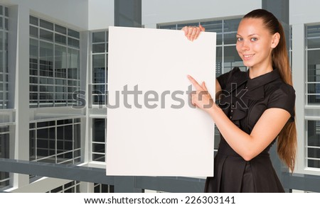 Businesswoman holding empty paper. Large window in office building as background