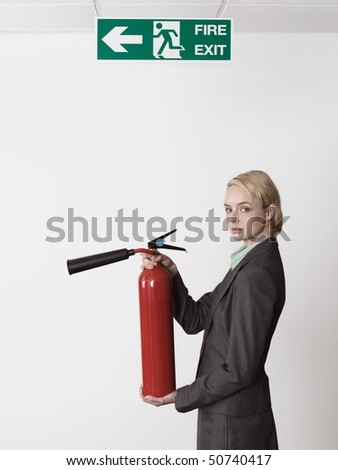 Businesswoman holding fire extinguisher under exit sign