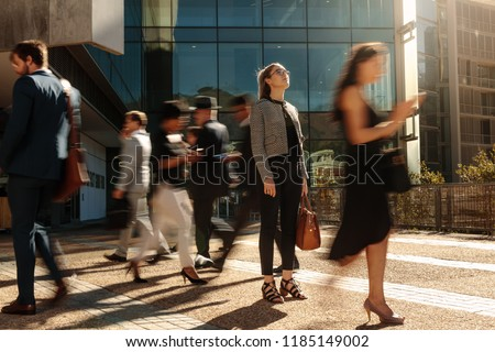 Businesswoman holding her hand bag standing still on a busy street with people walking past her using mobile phones. Woman standing amidst a busy office going crowd hooked to their mobile phones.