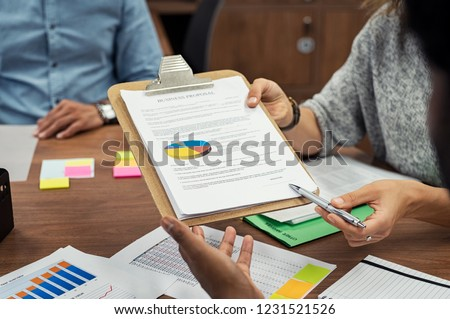 Businesswoman holding pen and pointing at signature place on a contract document. Closeup hands of casual business woman pointing finger on paper showing where to sign.