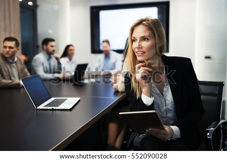 Businesswoman holding tablet at conference tablet having company meeting #552090028