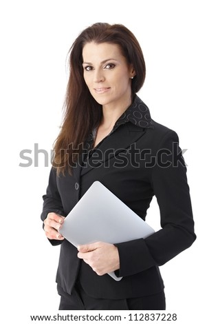 Businesswoman holding tablet pc smiling at camera.