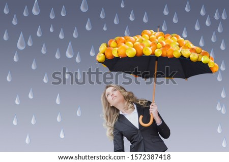 Businesswoman holding umbrella of fruit in rain against grey background