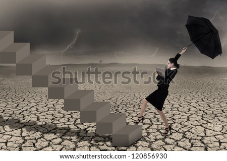 Businesswoman holding umbrella while walking up on stairs in stormy weather
