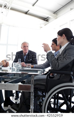 Businesswoman in a wheelchair during a meeting with her team