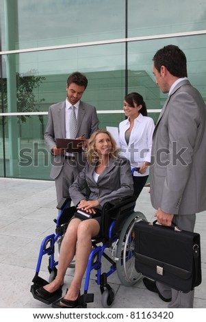 Businesswoman in a wheelchair with colleagues outside an office building