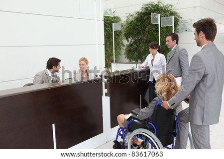 Businesswoman in a wheelchair with her colleagues at reception