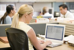 Businesswoman in cubicle using laptop