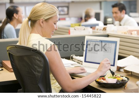 Businesswoman in cubicle using laptop and eating salad