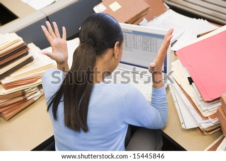 Businesswoman in cubicle with laptop and stacks of files