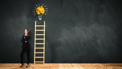 businesswoman in front of a blackboard with a ladder leading to a lightbulb symbol
