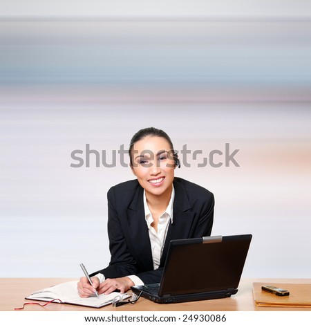 Businesswoman in front of the computer writes in a notebook. Please see some of my other business images: