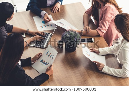 Businesswoman in group meeting discussion with other businesswomen colleagues in modern workplace office with laptop computer and documents on table. People corporate business working team concept. #1309500001