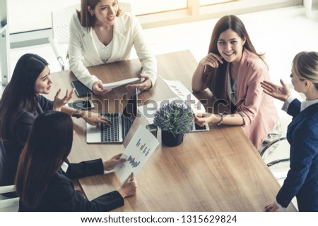 Businesswoman in group meeting discussion with other businesswomen colleagues in modern workplace office with laptop computer and documents on table. People corporate business working team concept. #1315629824