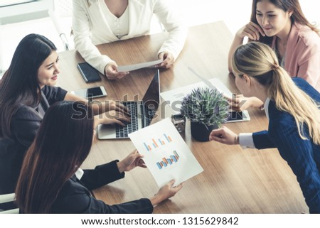 Businesswoman in group meeting discussion with other businesswomen colleagues in modern workplace office with laptop computer and documents on table. People corporate business working team concept. #1315629842