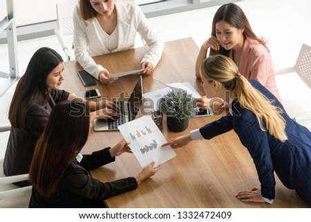 Businesswoman in group meeting discussion with other businesswomen colleagues in modern workplace office with laptop computer and documents on table. People corporate business working team concept. #1332472409