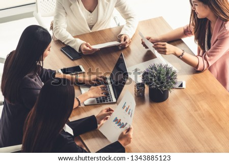Businesswoman in group meeting discussion with other businesswomen colleagues in modern workplace office with laptop computer and documents on table. People corporate business working team concept. #1343885123