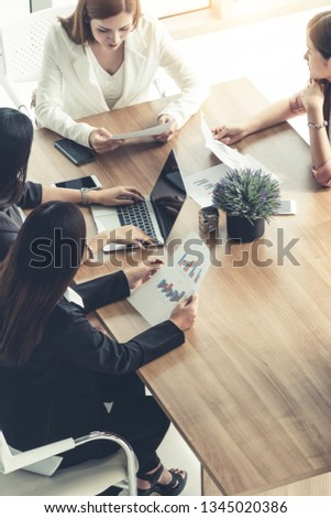 Businesswoman in group meeting discussion with other businesswomen colleagues in modern workplace office with laptop computer and documents on table. People corporate business working team concept. #1345020386