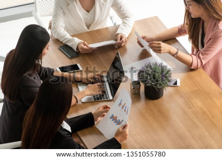 Businesswoman in group meeting discussion with other businesswomen colleagues in modern workplace office with laptop computer and documents on table. People corporate business working team concept. #1351055780